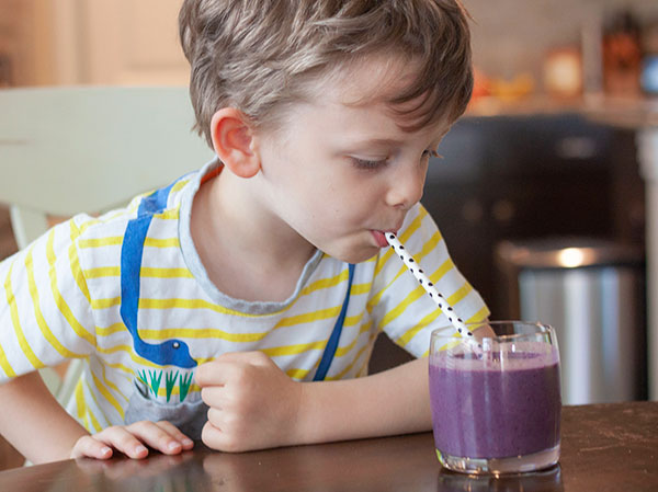 Toddler boy drinking a banana-berry smoothie (with hidden veggies!)