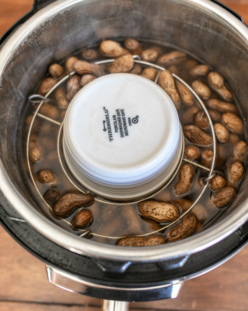 Peanuts in an Instant Pot, under a ramekin and trivet with water.